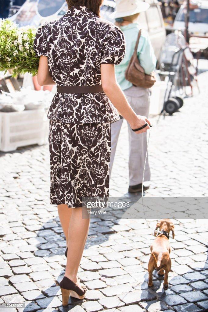 Caucasian woman walking dog on city street : Stock Photo