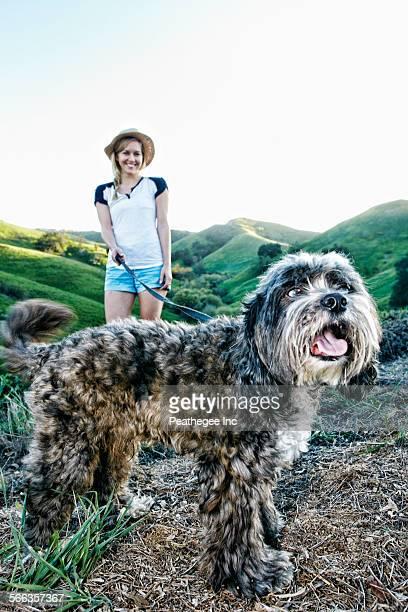 Caucasian woman walking dog on rural hilltop