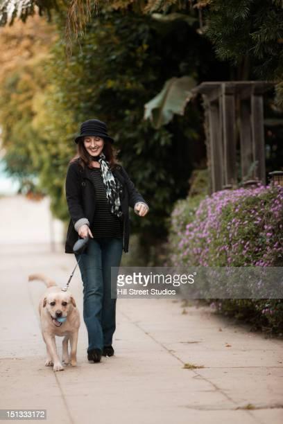 Caucasian woman walking dog