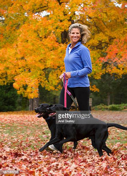 Caucasian woman walking dogs in park