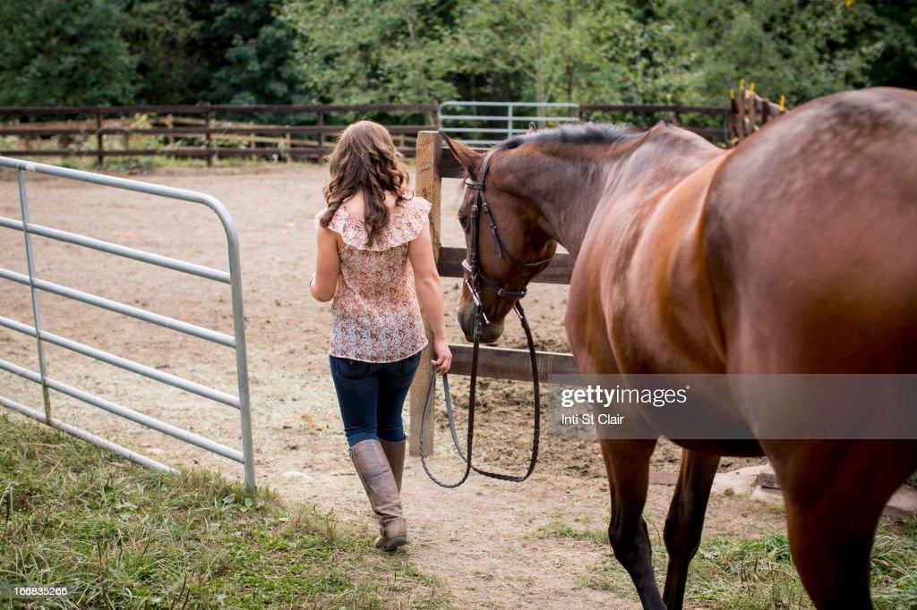 Caucasian woman walking horse in pen