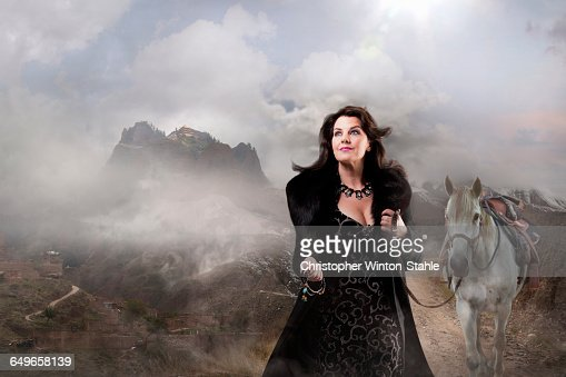 Caucasian woman walking horse in remote landscape : Stock Photo