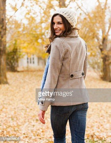 Caucasian woman walking in autumn leaves