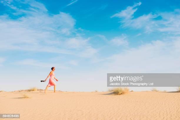 Caucasian woman walking in desert