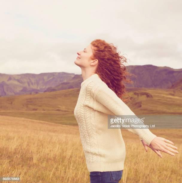 Caucasian woman walking in remote field