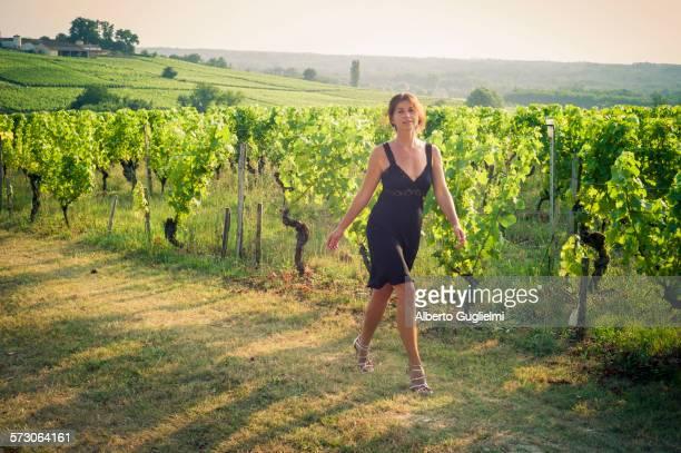 Caucasian woman walking on dirt path in vineyard