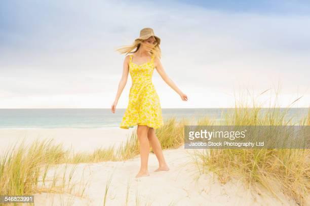 Caucasian woman walking on sand dune