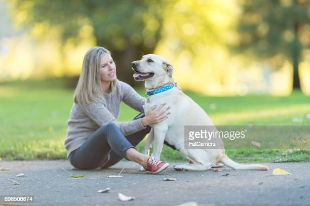 Caucasian woman walks her dog on beautiful summer evening in park