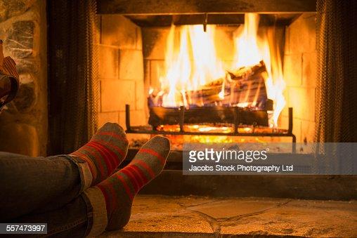 Caucasian woman warming feet near fireplace