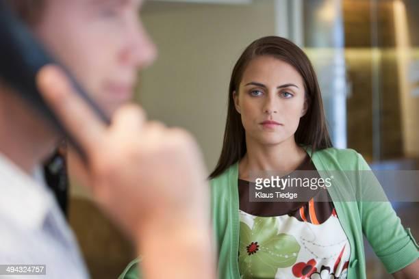 Caucasian woman watching boyfriend talk on cell phone