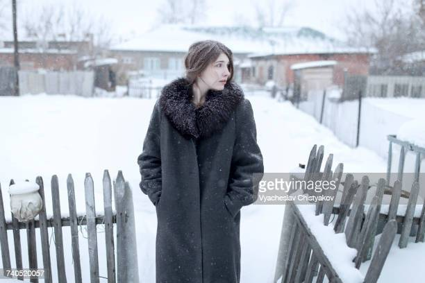 Caucasian woman wearing coat in winter near fence