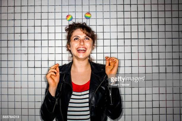 Caucasian woman wearing colorful antenna near wall