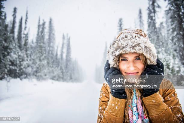 Caucasian woman wearing fur parka hood in snow