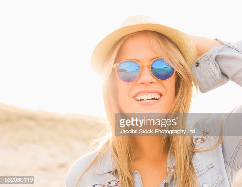 Caucasian woman wearing hat and sunglasses on beach