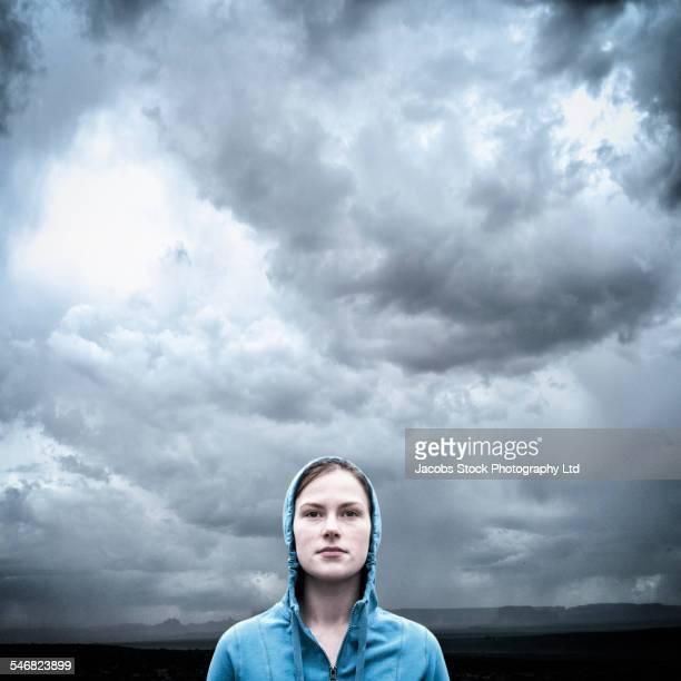 Caucasian woman wearing hoodie under stormy sky