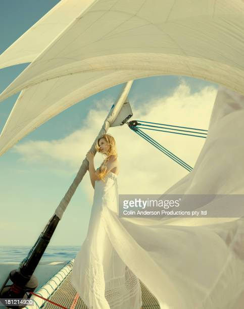 Caucasian woman wearing ornate gown on sailboat