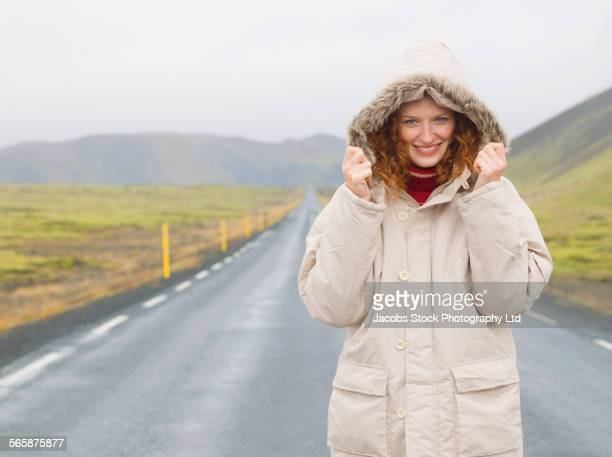 Caucasian woman wearing parka on remote road