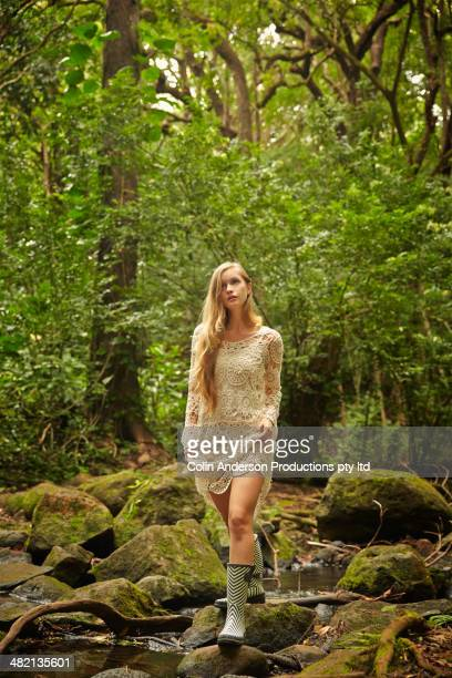 Caucasian woman wearing rain boots in woods