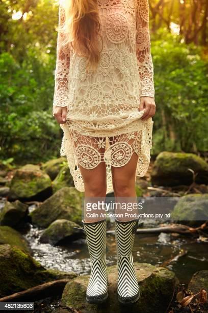 Caucasian woman wearing rain boots in woods