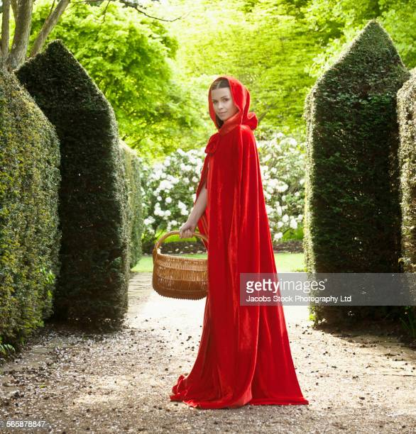 Caucasian woman wearing red cape in garden