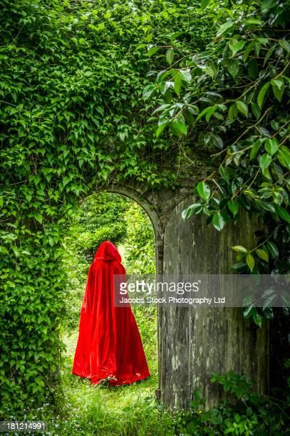Caucasian woman wearing red hooded cloak in garden