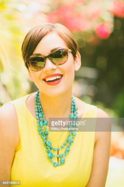 Caucasian woman wearing sunglasses and necklace outdoors