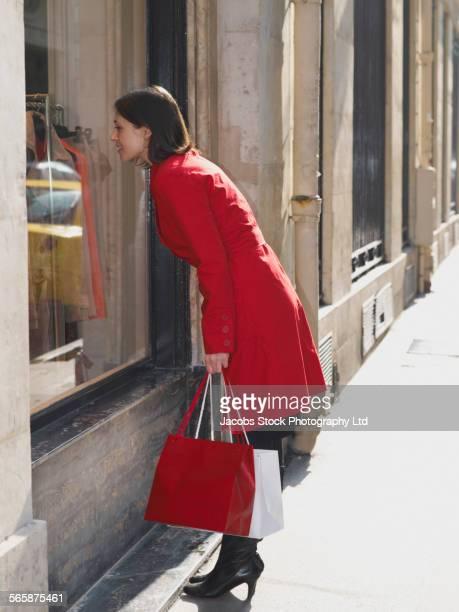 Caucasian woman window shopping on city sidewalk