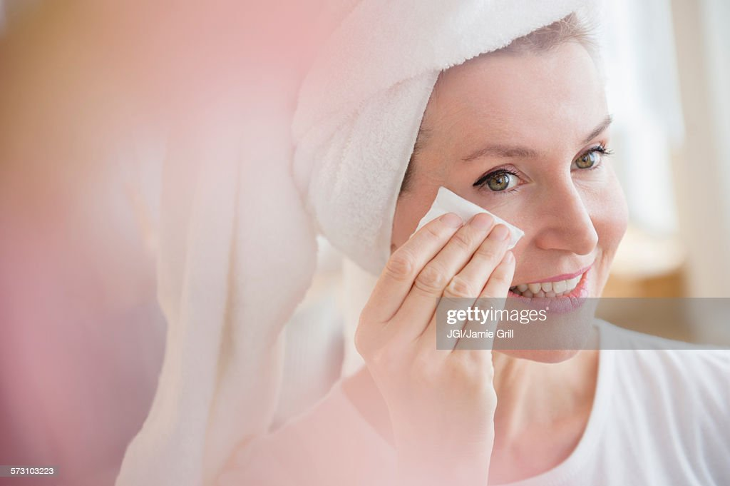 Caucasian woman wiping face : Stock-Foto