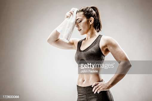 Caucasian woman wiping sweat from forehead