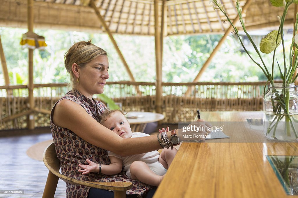 Caucasian woman with baby writing at table : Stock Photo