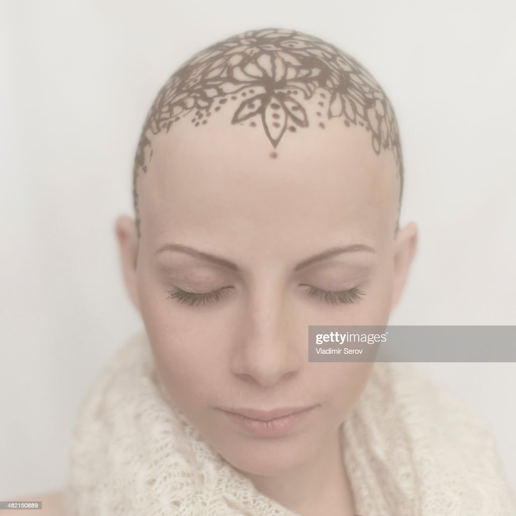 Caucasian woman with bald tattooed head : Stock Photo