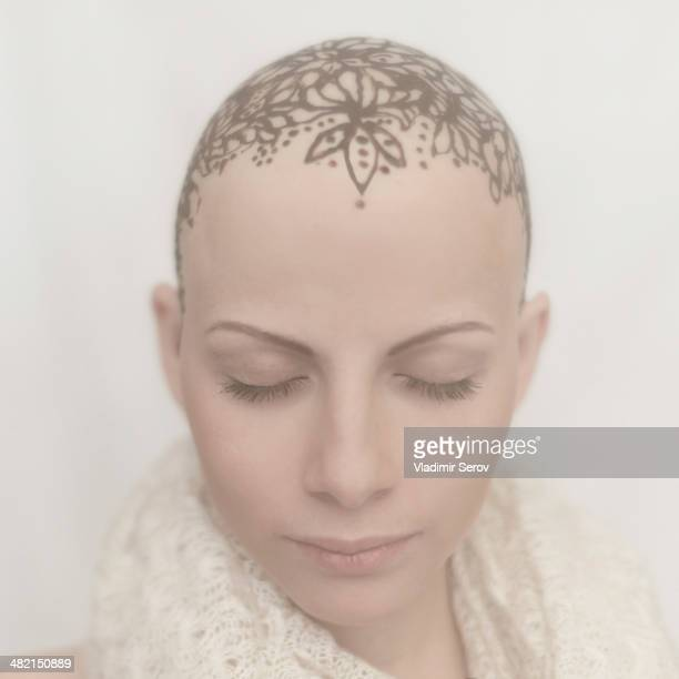 Caucasian woman with bald tattooed head
