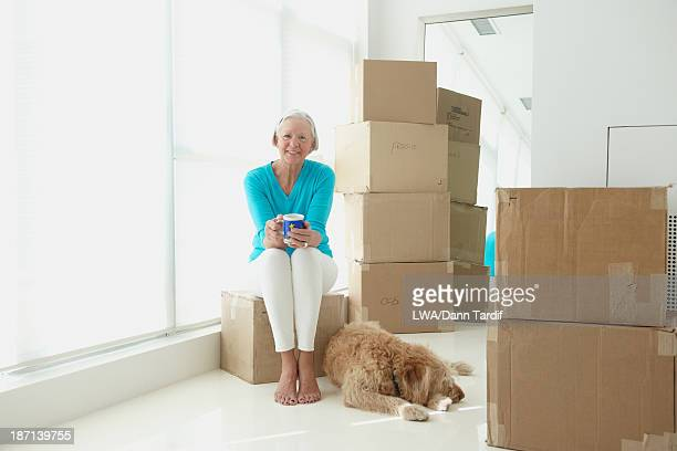 Caucasian woman with dog in new home