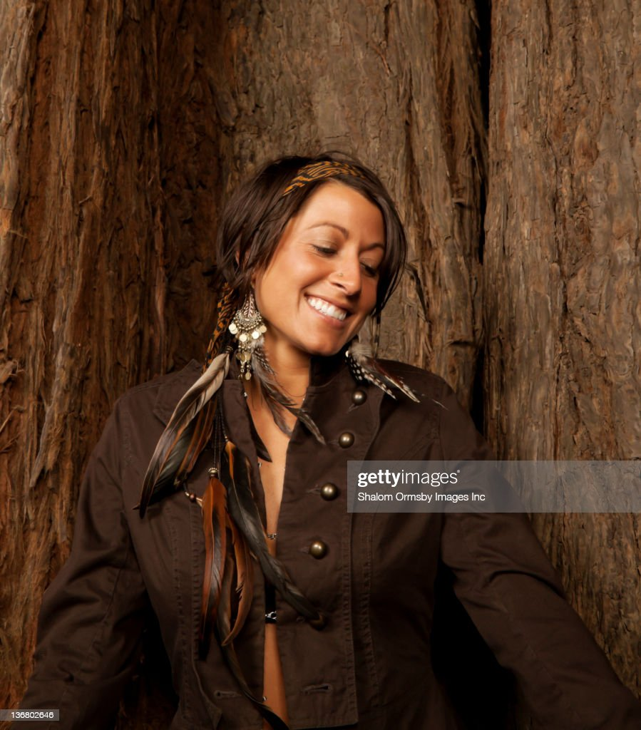 Caucasian woman with feather hair decorations near tree trunk : Stock Photo