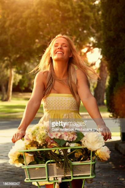 Caucasian woman with flowers in bicycle basket