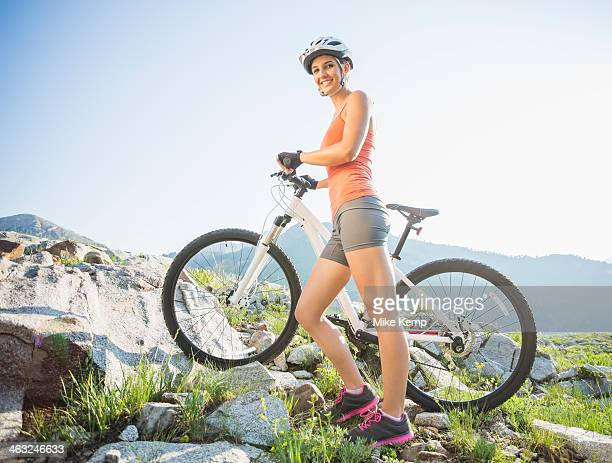 Caucasian woman with mountain bike on rocky hillside