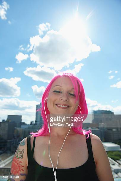 Caucasian woman with pink hair and tattoos listening to earbuds in city