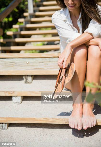 Caucasian woman with sandy feet sitting on beach staircase