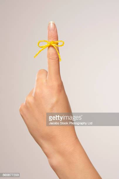 Caucasian woman with string tied around finger
