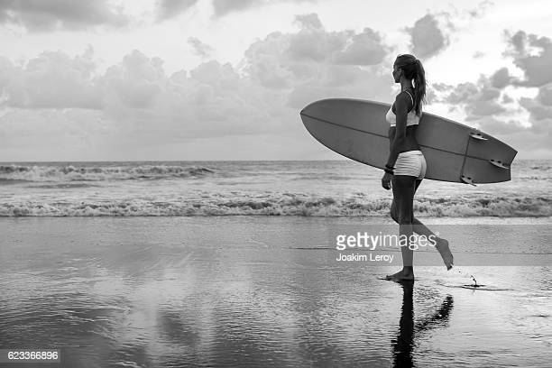 Caucasian woman with surfboard on the beach going to surf