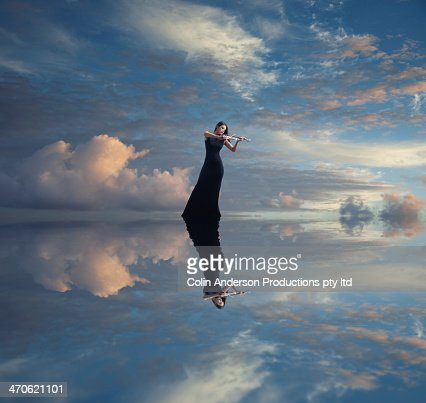 Caucasian woman with violin reflected in still lake