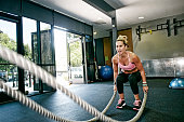 Caucasian woman working out with ropes in gym