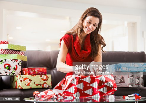 Caucasian woman wrapping Christmas presents in living room