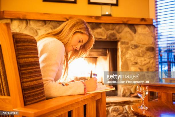 Caucasian woman writing in journal near fireplace