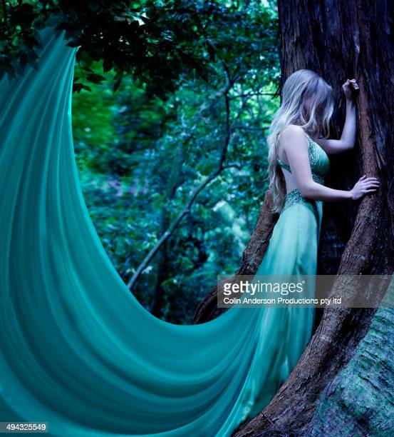 Caucasian woman's dress caught on tree in forest