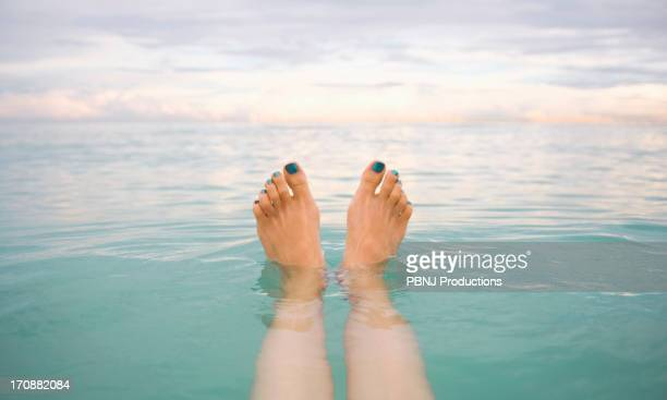 Caucasian woman's feet floating in tropical water