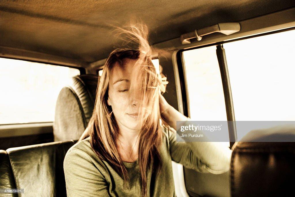 Caucasian woman's hair blowing in car : Stock Photo