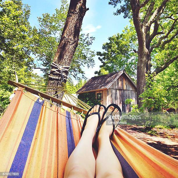 Caucasian woman's legs feet on a colorful hammock in the backyard in Westford MA