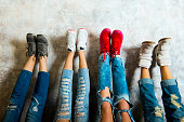 Caucasian women admiring their sneakers against wall