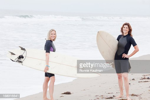 Caucasian women carrying surfboards : Stock Photo